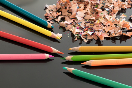 sharpened: Sharpened colorful pencils and pile of colorful pencil shavings on black glass gloss table, with medium depth of focus