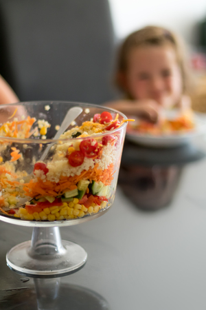 multi layered: Multi Layered Salad in a Glass Trifle Bowl on on a glass table top, with little girl in background, narrow depth of focus.