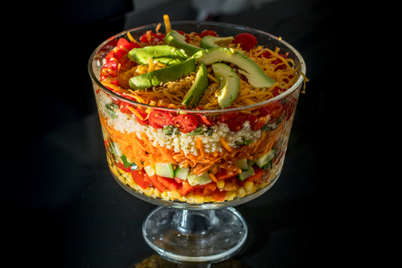 multi layered: Multi Layered Salad in a Glass Trifle Bowl on black background