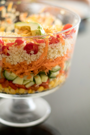 multi layered: Healthy Multi Layered Salad in a Glass Trifle Bowl on on a glass table top, shot with narrow field of focus