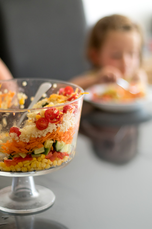 trifle: Multi Layered Salad in a Glass Trifle Bowl on on a glass table top, with little girl in background, narrow depth of focus.