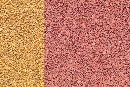 floor covering: Rubber play ground floor surface covering, colorful yellow and red, straight edge Stock Photo
