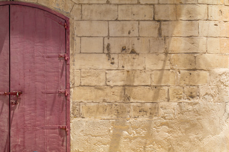 creed: Locked red wooden double-door, in Maltese Limestone wall, shot straight-on in Valletta, Malta, Europe. Used in the 2015 filming of the Assassins Creed movie. Stock Photo