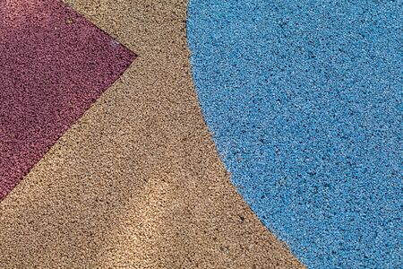topdown: Colorful red, yellow and blue Rubber Wetpour playground floor surface. Stock Photo
