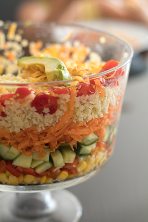 trifle: Healthy Multi Layered Salad in a Glass Trifle Bowl on on a glass table top, shot with narrow field of focus