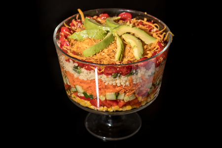 trifle: Multi Layered Salad in a Glass Trifle Bowl on black background
