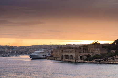 Beautiful colorful sunset over Manoel Island, looking towards Misda, shot from Marsamxett Harbour, Malta.