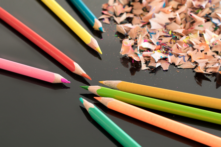 sharpened: Sharpened colorful pencils and pile of colorful pencil shavings on black glass gloss table, with shallow depth of focus