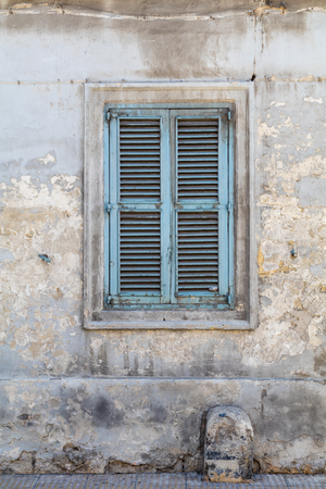 creed: Traditional Maltese blue wooden window, with shutters and fading paint.  Crumbling wall, shot straight-on in Valletta, Malta, Europe. Used in the 2015 filming of the Assassins Creed movie. Stock Photo