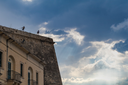 rappeling: workers absail to repair the crumbling fortifications surrounding Valletta, backed by a dramatic sky, June 2016.