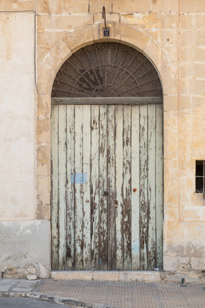 creed: Ancient light green wooden doorway with flaking paint, shot straight-on in Valletta, Malta, Europe. Used in the 2015 filming of the Assassins Creed movie.