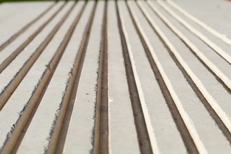 flute structure: close of of concrete bench showing ridges, shot with shallow field of focus