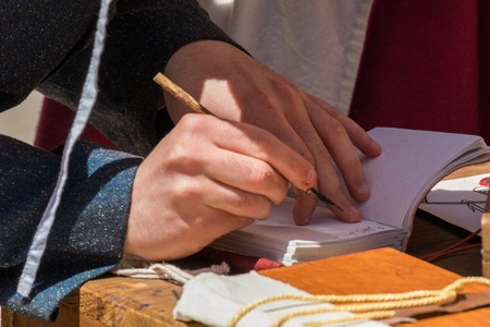Close up of hands of scribe practicing traditional illumination writing calligraphy with feather quill and ink