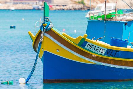 Traditional colourful Maltese Luzzu fishing boats in the turquoise blue water of Marsaxlokk harbour, Marsaxlokk, Malta, June 2017