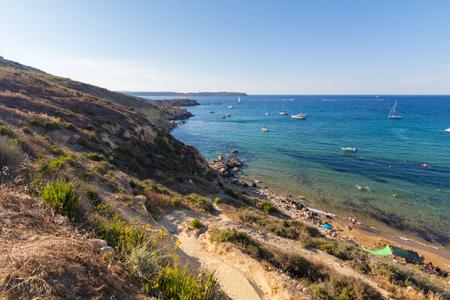 Beautiful azure blue water of Selmun beach in the summer time, in Maltese Imgiebah Bay, Il-Mellieha, Malta, Stock Photo