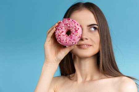 Close-up of a woman with long hair holding a donut . Female model a donut in front of her face on blue background.