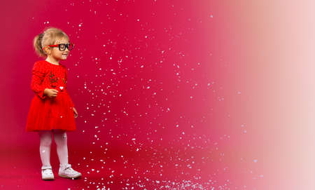 WOW- let it snow. Holiday and fashion concept. Little girl in Xmas dress and glasses playing with snowflakes. Cute beauty isolated on red to white background. Get ready for winter holiday.