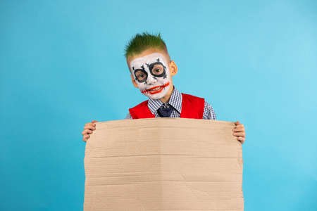 Orizontal shot of funny boy, activist wearing carnival costume on halloween holiday with empty sign board, ooking at camera. Isolated on blue background with free side space.