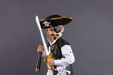 Classic captain pirate with face painted lunging forward with raised sword in challenging pose. Isolated on gray background with plenty of room for copy. Happy Halloween