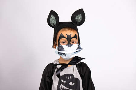 Happiest Halloween in new reality of COVID-19 pandemic. Portret of boy disguised like bat with black hat with big ears. He is wearing protective medical mask with a funny smile painted. Standard-Bild