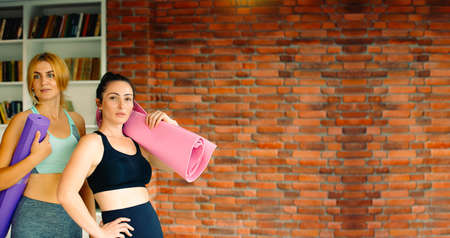 Healthy lifestyle and sports. Women with sports mats are ready for training in a good mood. Studio background with empty space Zdjęcie Seryjne