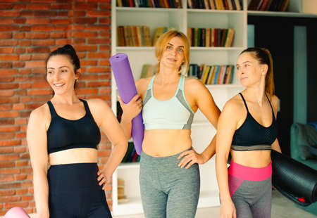 Healthy lifestyle and sports. Energetic girls with sports mats are ready for training in a good mood.