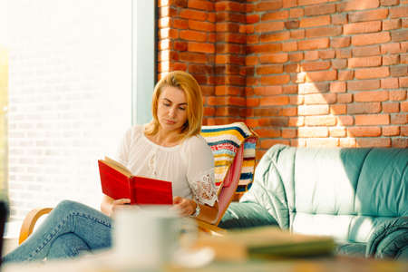 Young attractive woman reads a book, sitting in a comfortable rocking chair. A good pastime improves your mood.