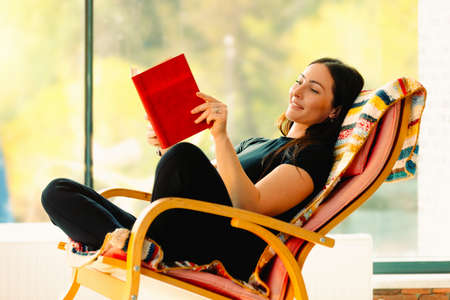 Young attractive woman reads a book swaying in a comfortable rocking chair. Having fun and having a good time improves your mood.