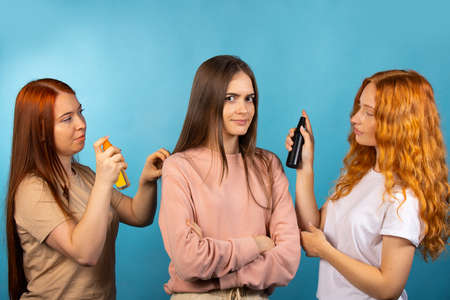 Aroma testing. Two consultant girls are testing new fragrances on a third girl. Hairstyling product tester. Photo on blue background. High quality photo Reklamní fotografie