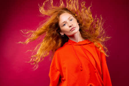 Portrait of a beautiful red-haired girl with flying curly hair looking at the camera on a red background. High quality photo