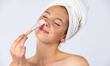 A girl with a towel on her head and hangs on her face, applies a gel mask with a brush. Fashionable female model with beautiful appearance. Photo on white background. High quality photo