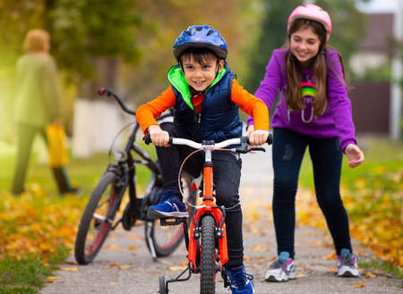 Autumn day. Sister teaches her little brother to ride a bike and rejoices at his success. Family and healthy lifestyle. High quality photo