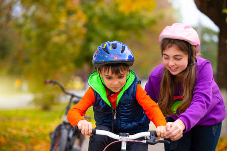 Striving for success. A sister teaches her little brother to ride a bike in the park. Autumn. Family and healthy lifestyle. High quality photo Stock Photo