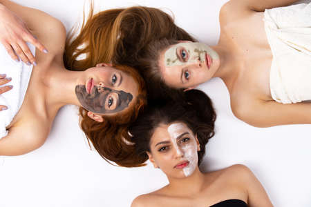 Three girls, girlfriends with different half-face masks, lie on the floor, wrapped in towels. Healthy skin and beauty concept on white background. High quality photo Stok Fotoğraf