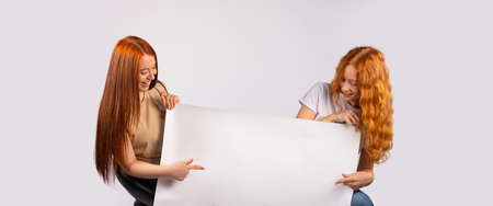 Two red-haired girls are holding a large white poster that might contain your ad. Photo on white background. High quality photo Stok Fotoğraf