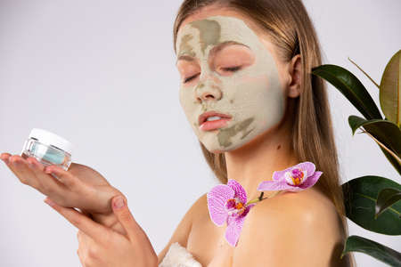 A sweet girl with long hair and a clay face mask, with a cream in her hands. Skin care, spa and beauty concept. High quality photo Banque d'images