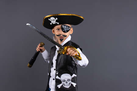 Classic pirate captain with painted face, sword and telescope. Isolated on a gray background with plenty of copy space