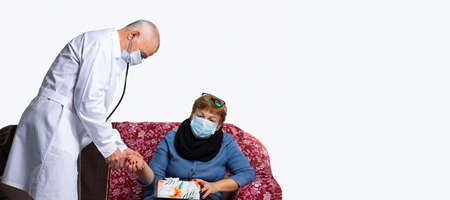 A masked doctor checking woman pulse during a medical examination at home. Virus and pandemic.