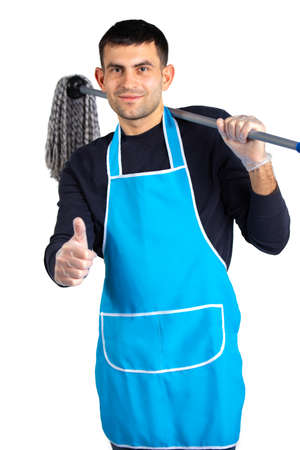 A man in an apron, gloves and a mop on his shoulder poses and shows the class to the camera. Gender inclusivity. Photo on white background with empty side space.