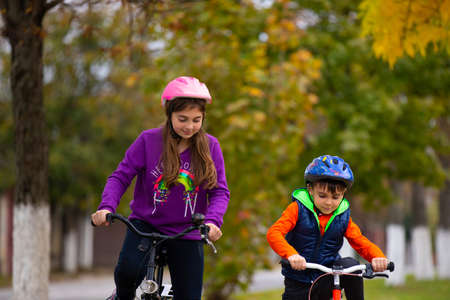 Children on bicycles and in protective helmets, ride in the autumn city park. In the photo, trees blurred behind