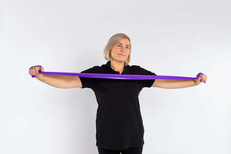 Sporty senior woman on a white background stretches the fitness elastic band in her hands. Healthy lifestyle and pandemic concept.