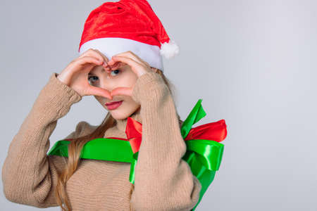 A gentle girl in a Santa hat looks through heart made by hands, heart sign, giving back charity . High quality photo