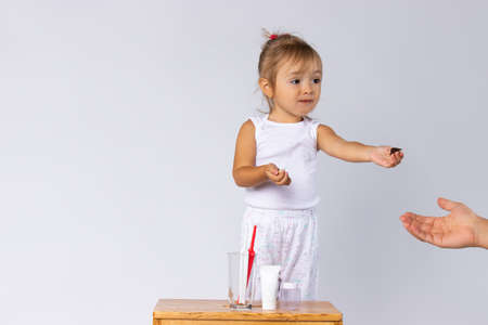Little girl in pajamas, and a baby kit for brushing teeth. White background and empty space. Hygiene. High quality photo