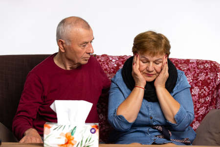 Older man is caring for a sick wife who suffers from headaches. Home treatment.