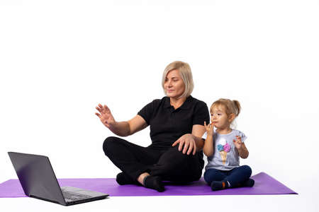 Senior woman sitting on a fitness mat with her granddaughter. Waving hand at laptop camera. Fitness online. High quality photo
