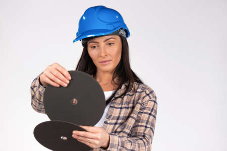 Handywoman in hardhat examines the abrasive disc for grinder. White background. High quality photo