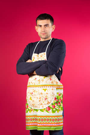 Serious young man in a kitchen apron on a pink background. The concept of gender stereotypes. High quality photo