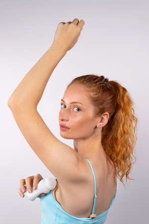 Young red-haired girl with antiperspirant looks at the camera on a white background. Body care. High quality photo