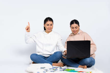 One of the female twins got an idea. White background, laptop and puzzle. Sisters spending time at home. High quality photo