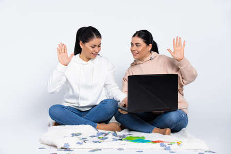 Twin girls with a laptop and puzzles are sitting on the floor at home, waving to video conversation. White background. High quality photo
